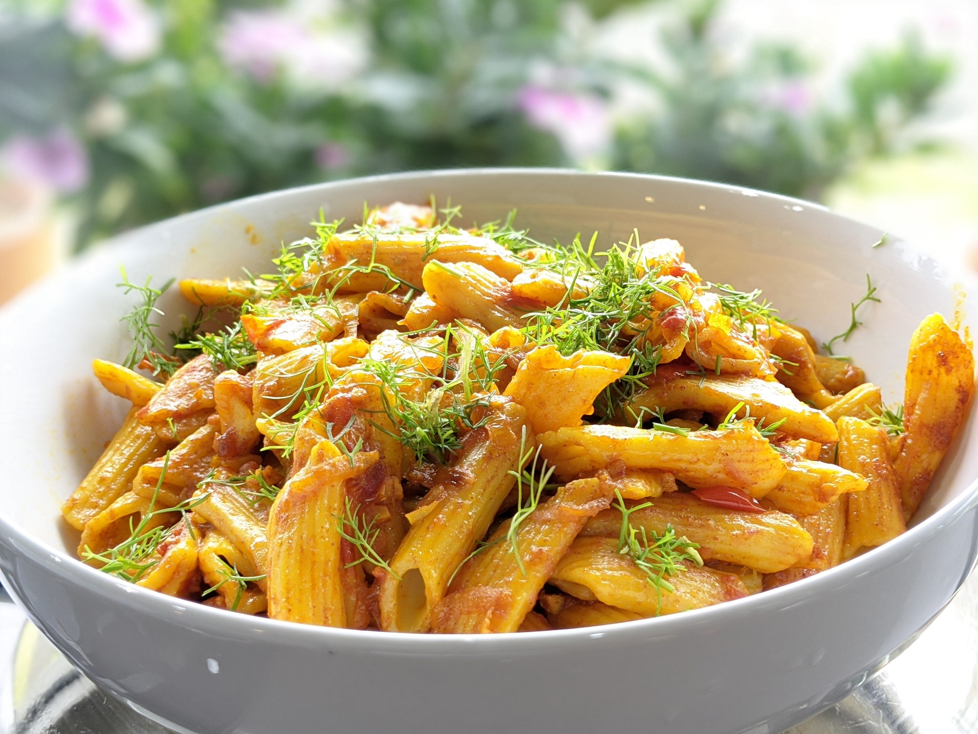 Cooked penne pasta with tomatoes and coriander